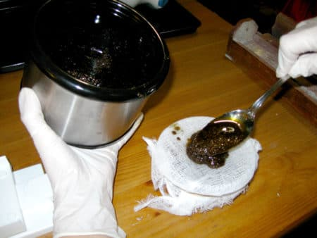 Spooning cooked cannabis-laden oil onto filter cheesecloth