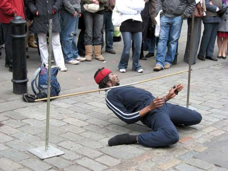 A performer doing limbo live on the street
