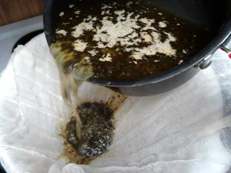 Pour weed butter mixture through the cheese cloth to strain out all the plant matter